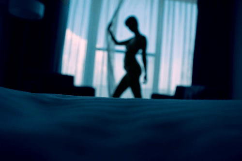 silhouette of woman in front of window