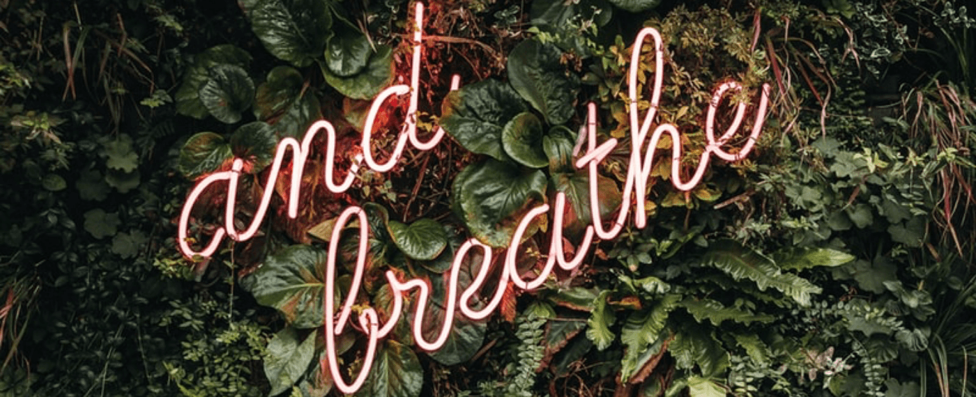 a neon sign that says breathe to help with breathing and stress
