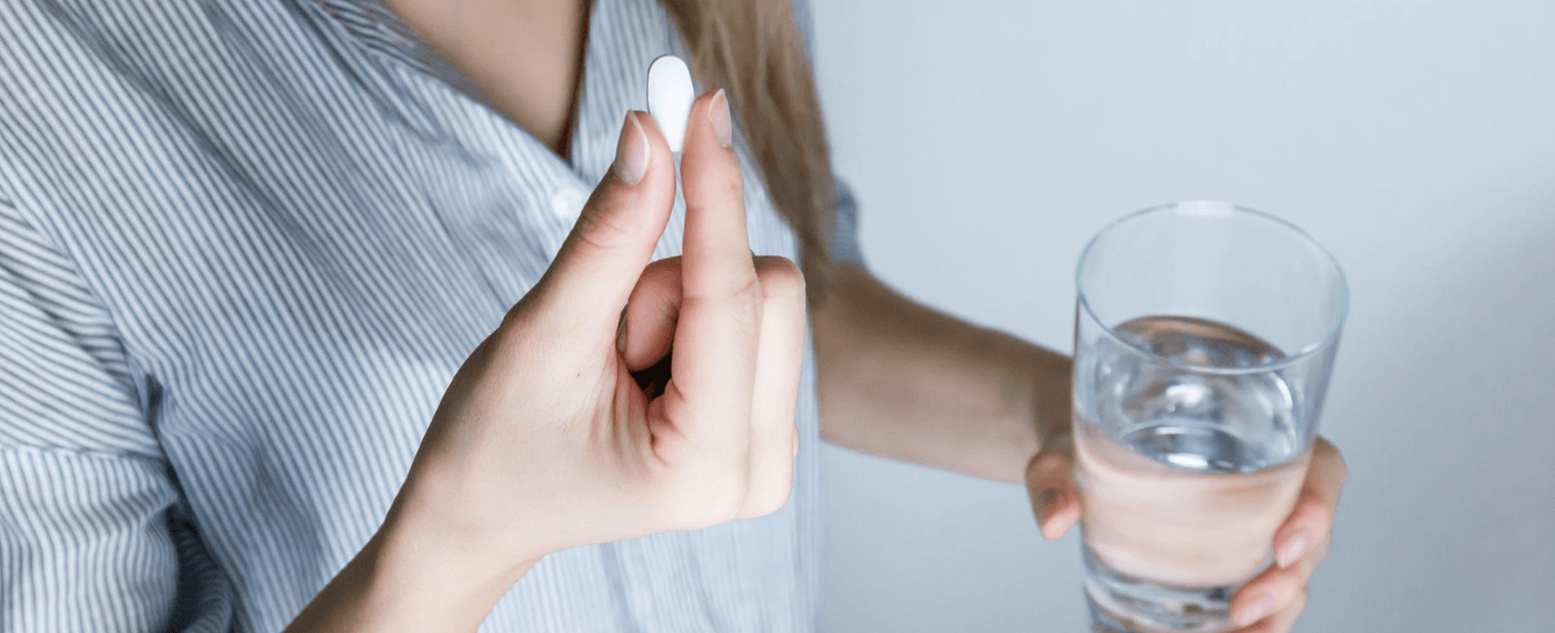 woman with a glass of water taking a probiotic for gut health