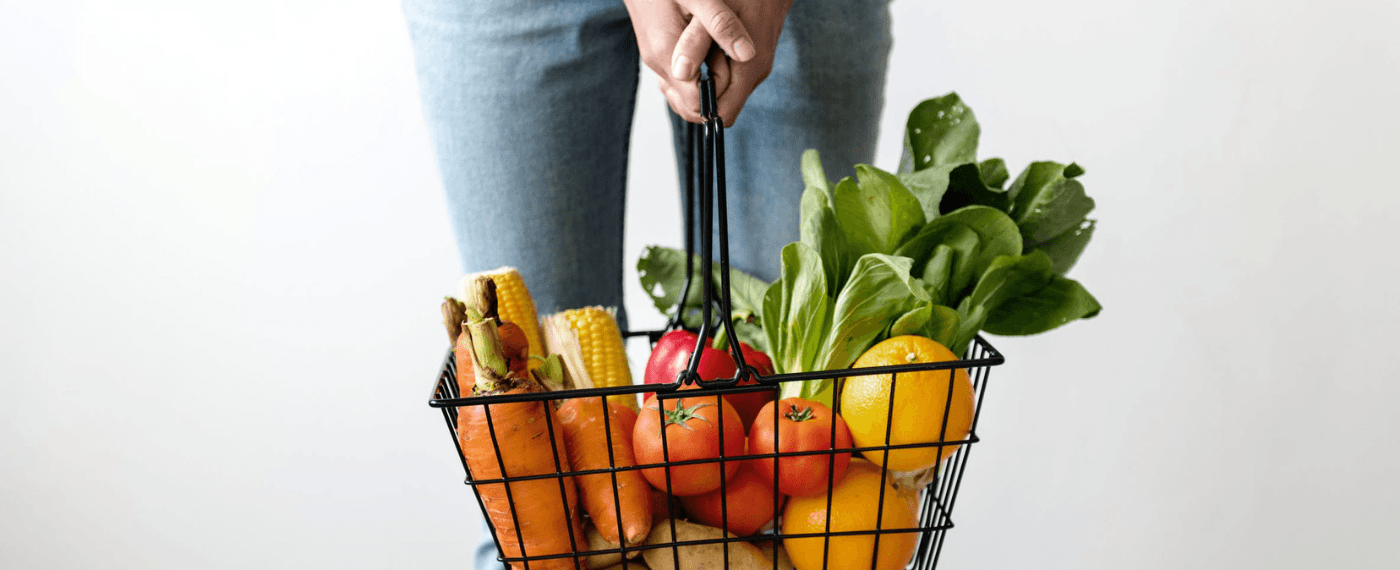 woman holding grocery basket full of fresh vegetables
