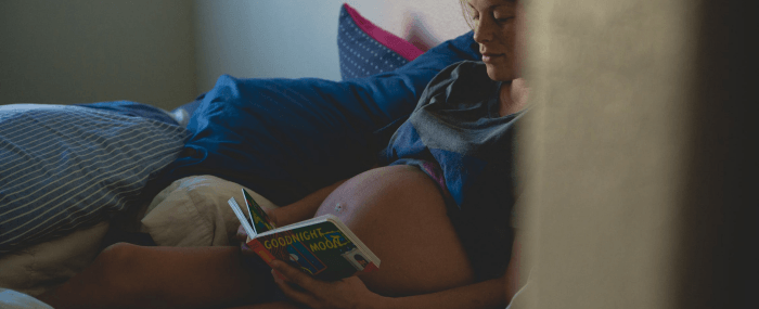 expecting mother reading book about the do's and don't during pregnancy