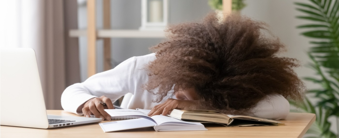 A tired teenager asleep at her desk during studies