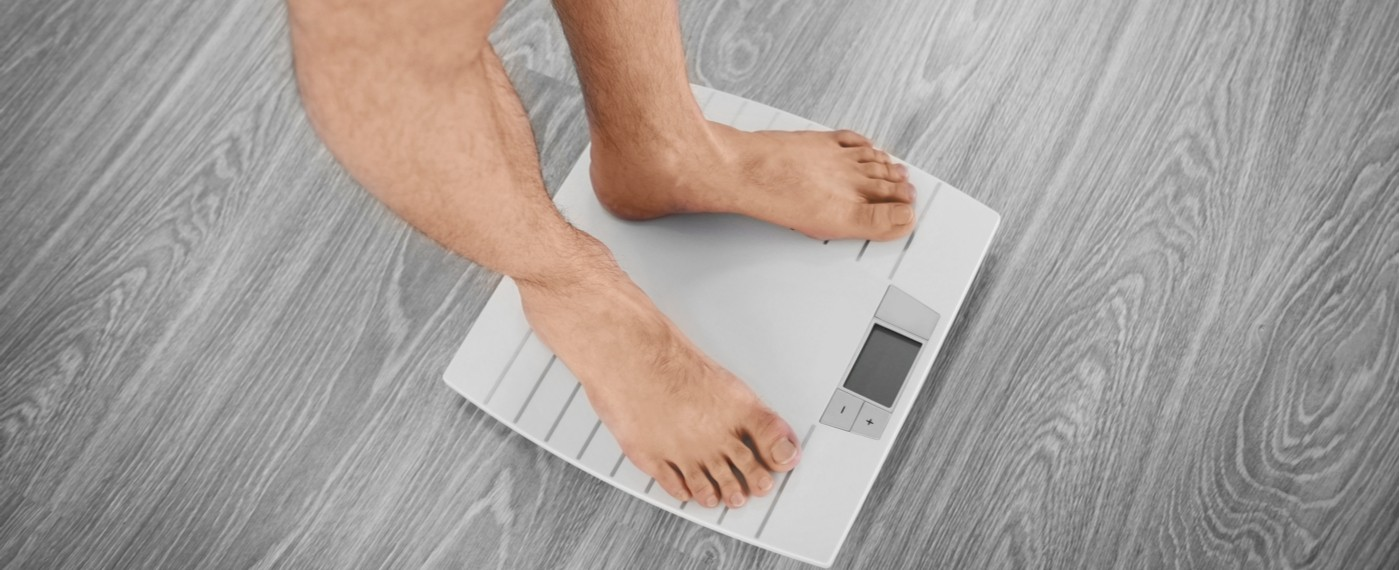 man on scale weighing himself