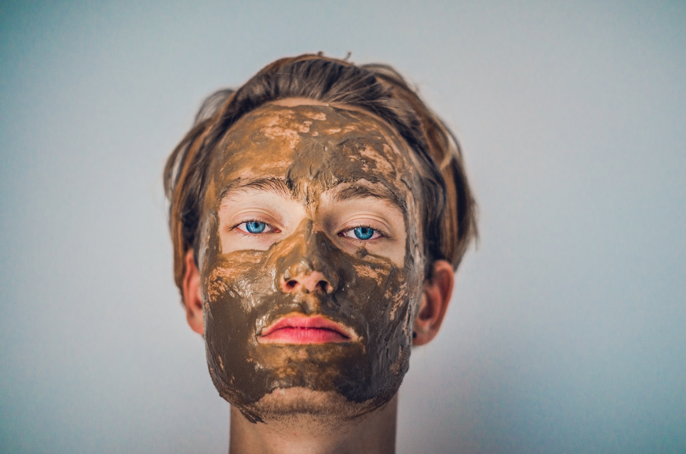 a woman using a mud face mask as part of her skin care routine
