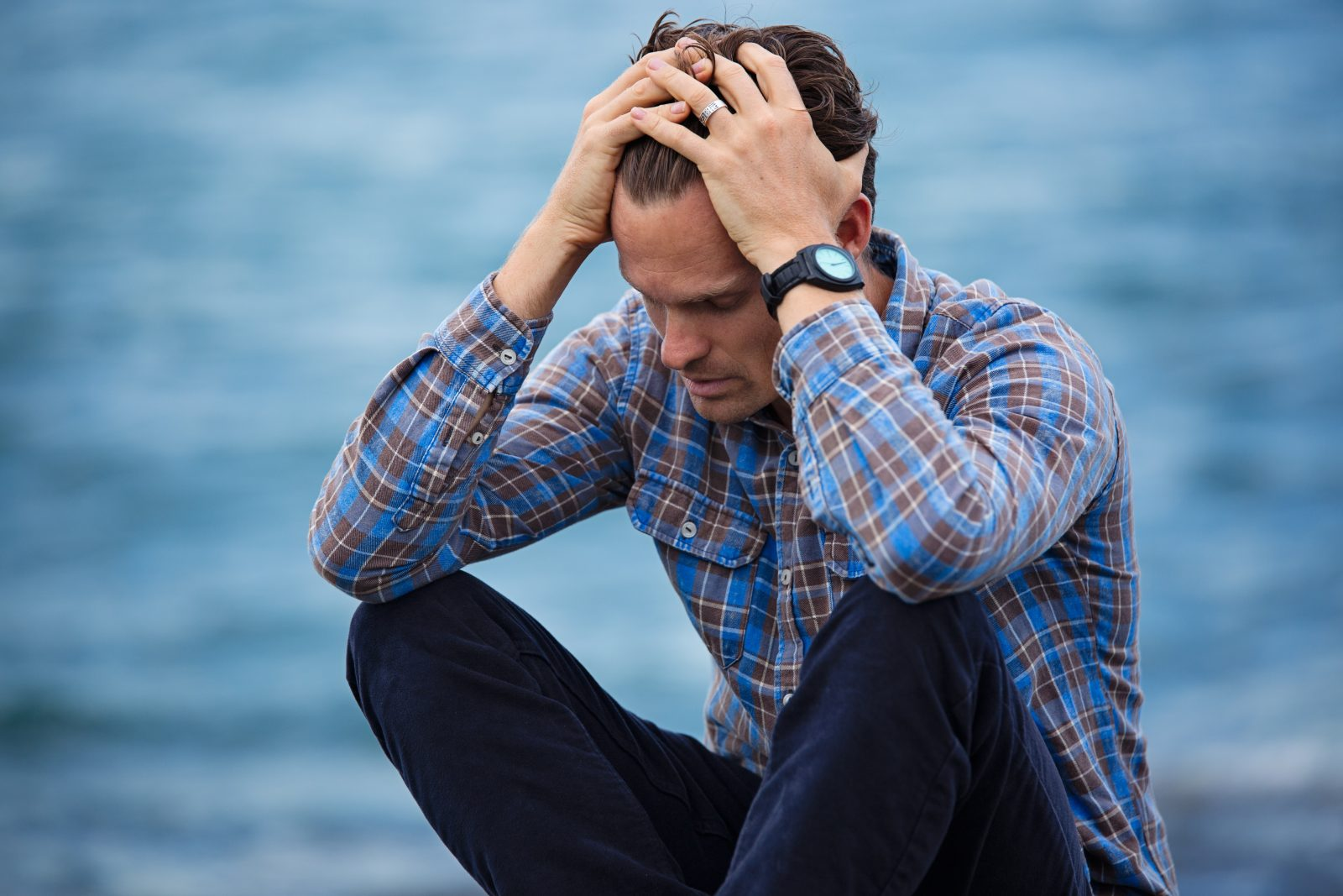 Man sitting cross legged, stressed out with hands running through hair