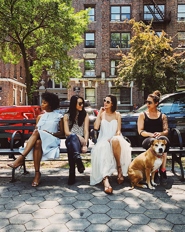 A group of women with a dog sitting and talking on a bench