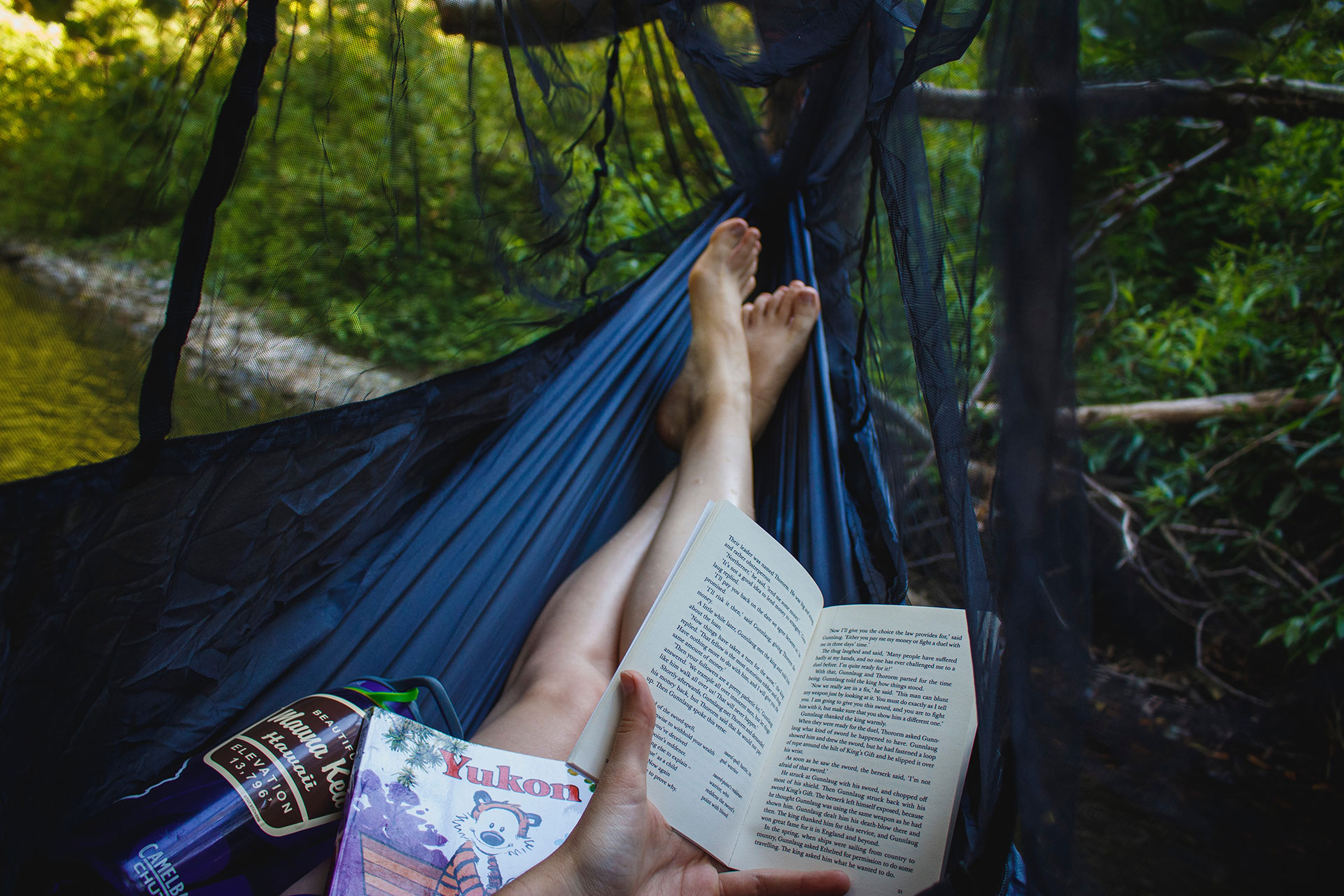 woman reading a book in a hammock by a river as part of her self care routine