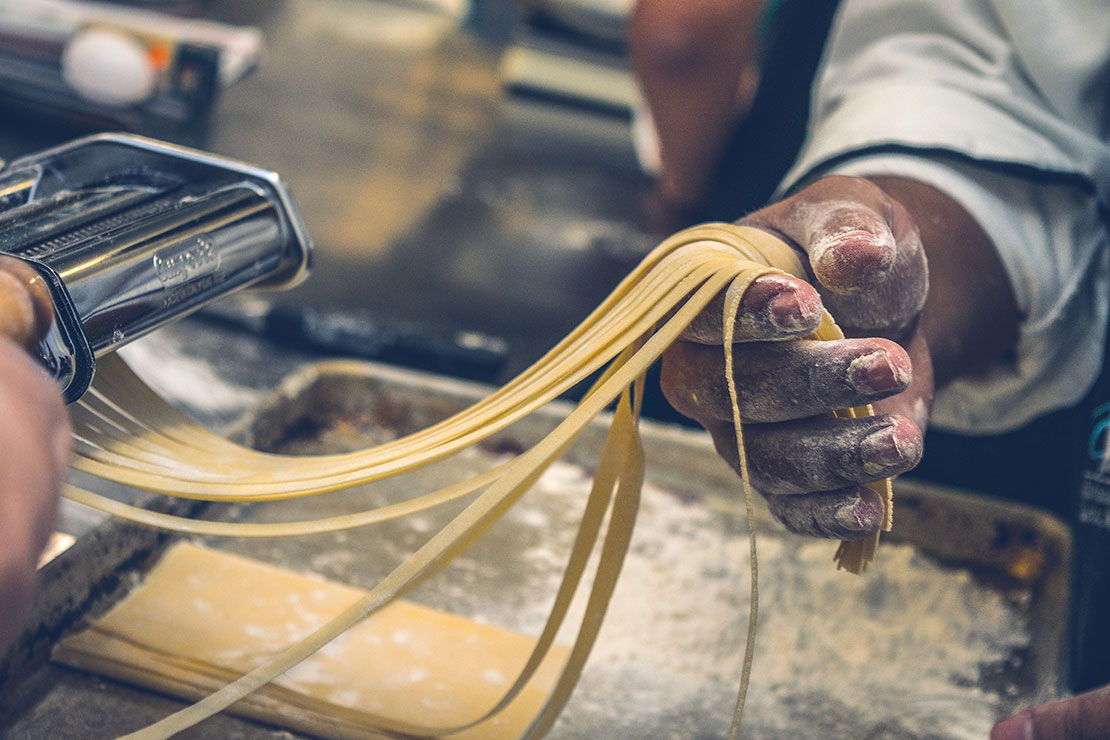 Fresh pasta being created with a pasta maker