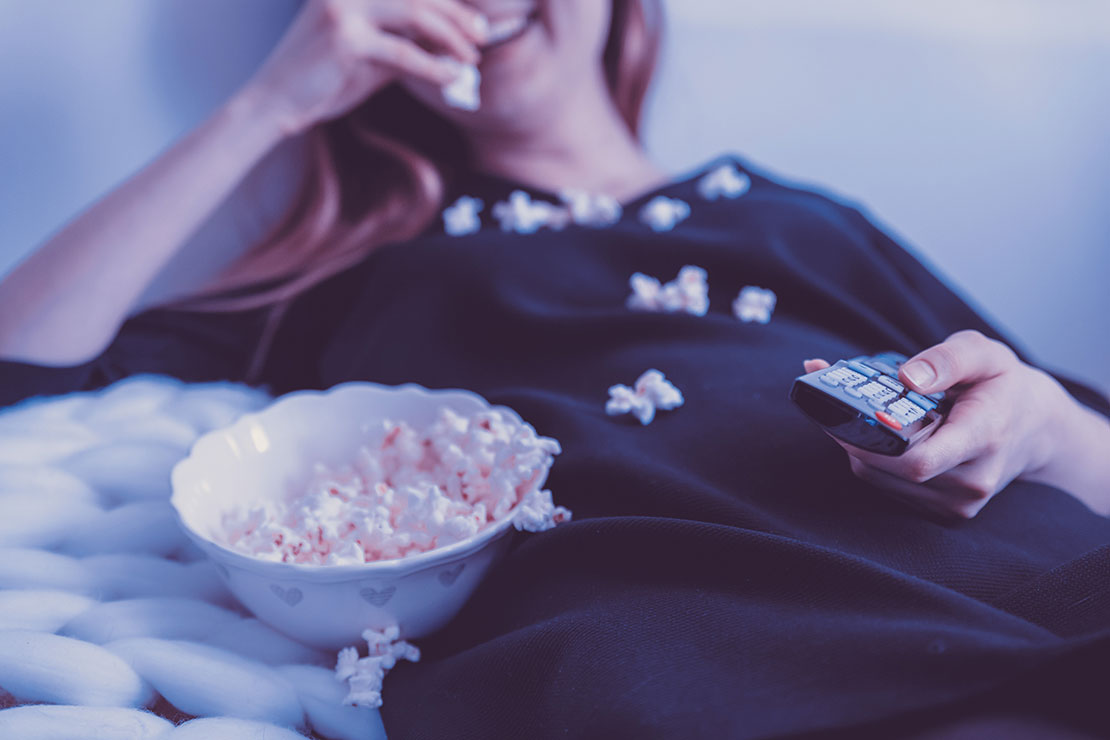 Woman laughing while eating a bowl of popcorn and watching tv