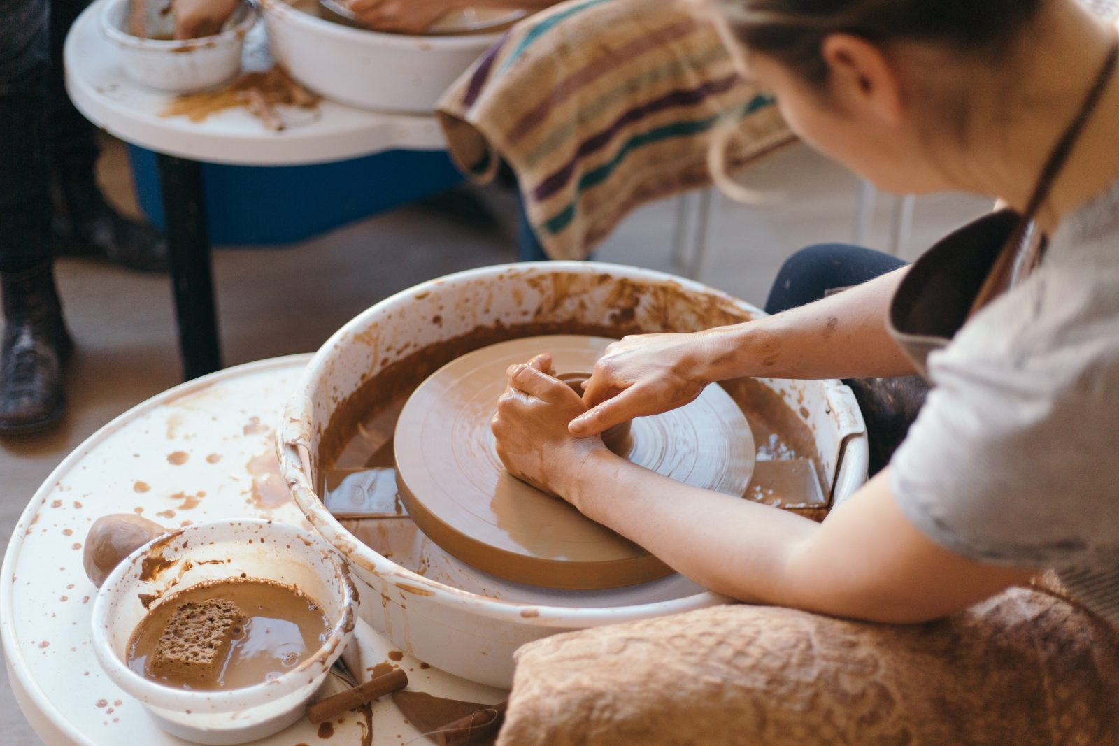 Woman engaging in forming pottery