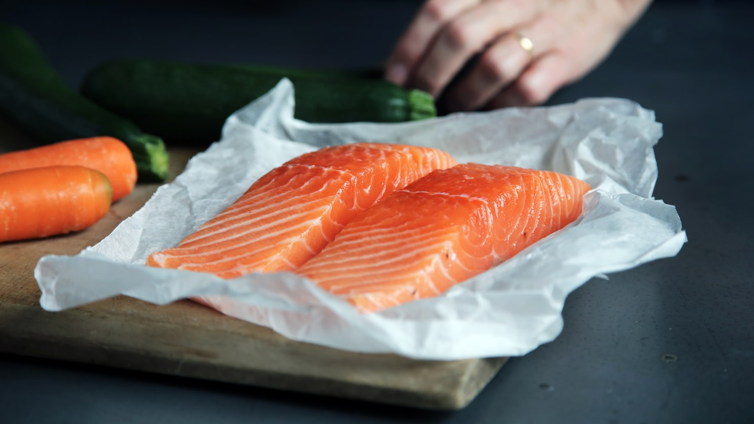 Parchment paper with two pieces of salmon