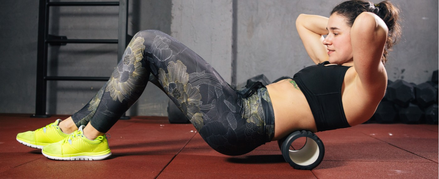 fitness girl using back roller to help stretch muscles for pain management
