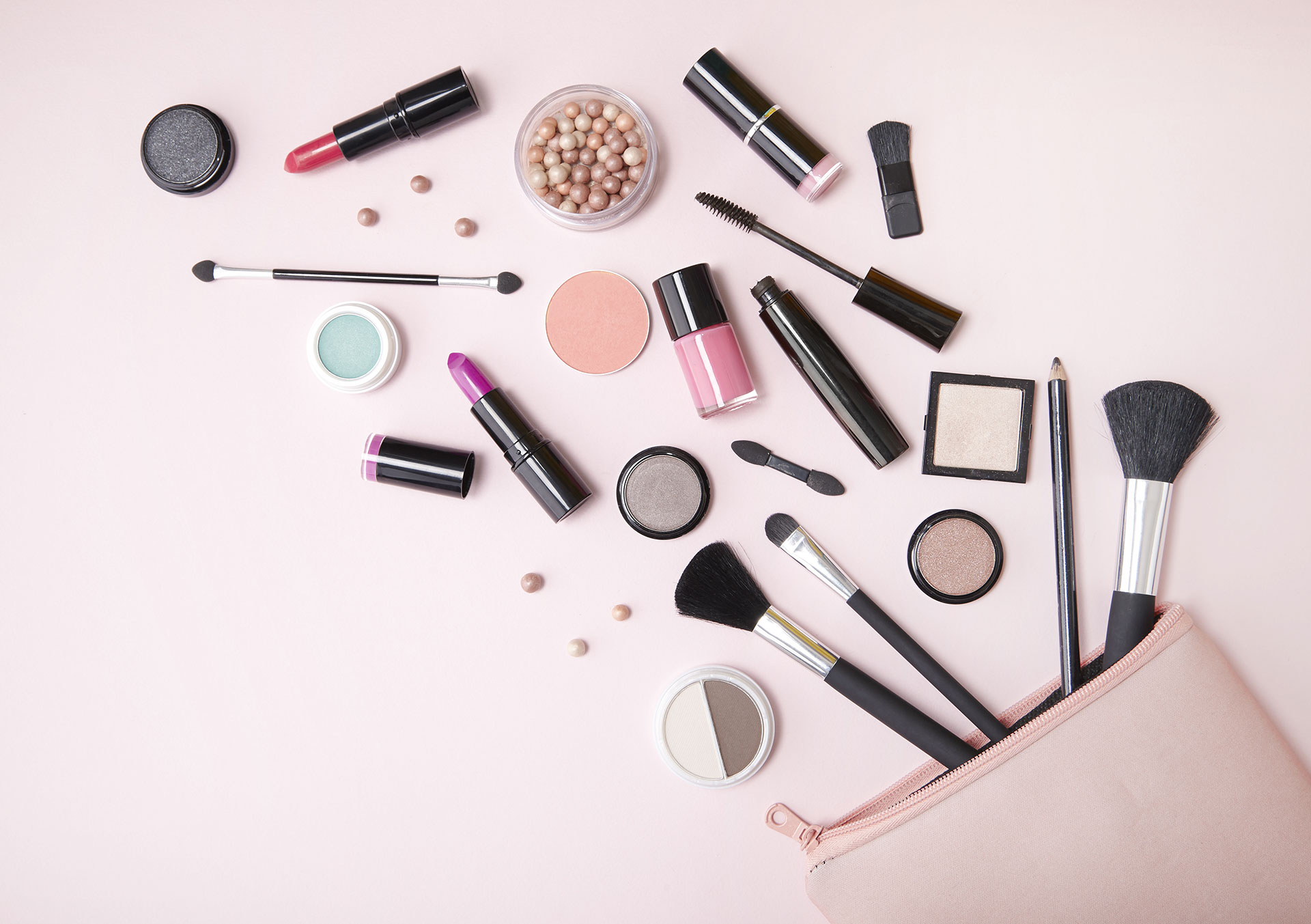 A variety of makeup products with endocrine disrupting chemicals and brushes spilling out of a bag