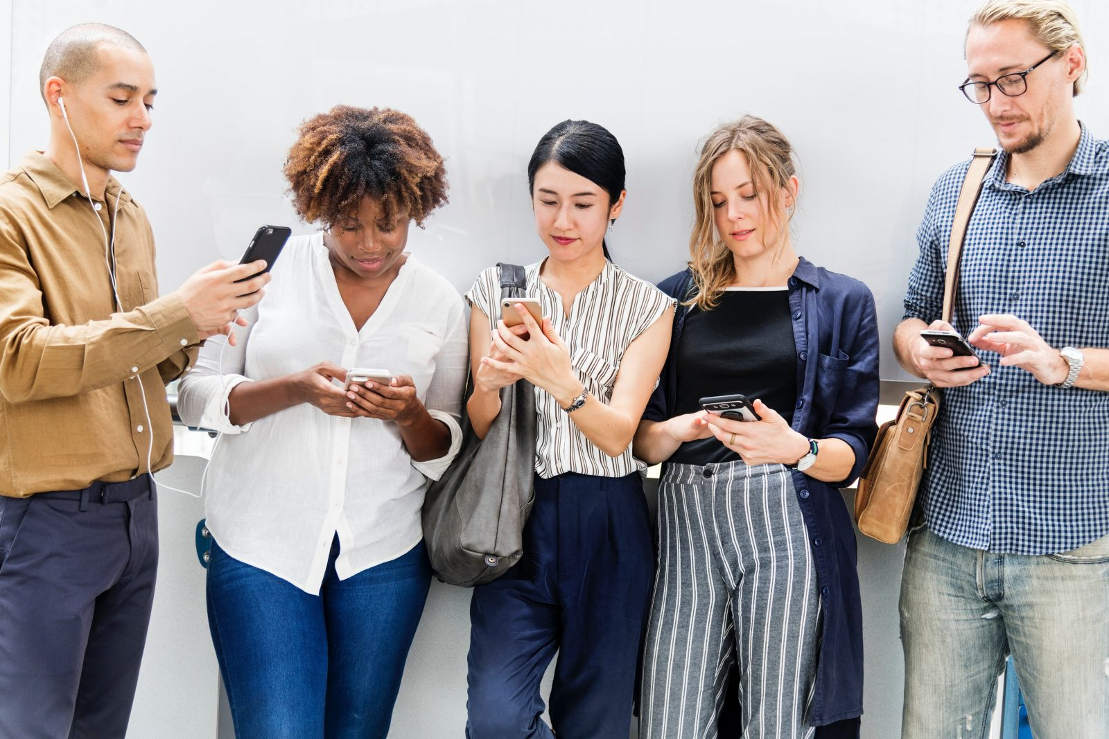 A group of men and women checking their cellphones