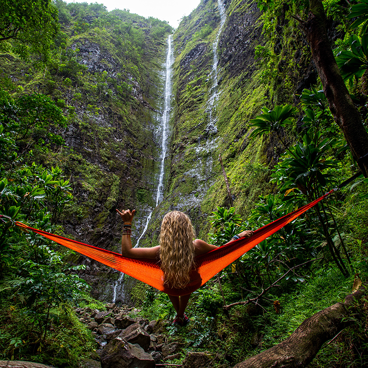 Woman relaxing in a hammock overlooking a waterfall in a rain forest