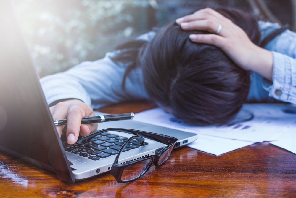 business woman with hand on head and face down on desk