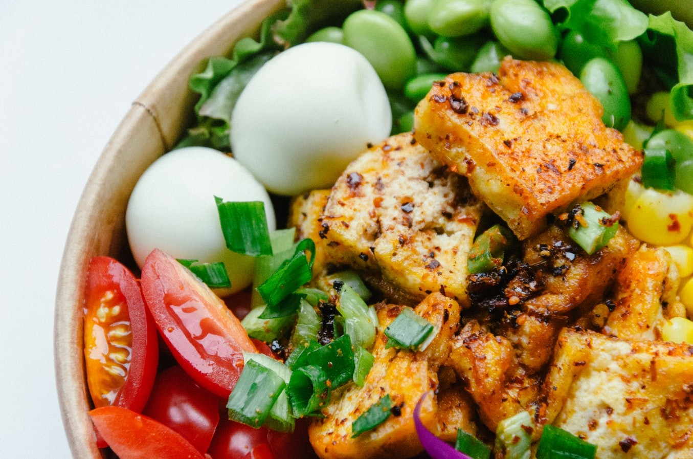 A bowl of tofu with vegetables and hard boiled eggs