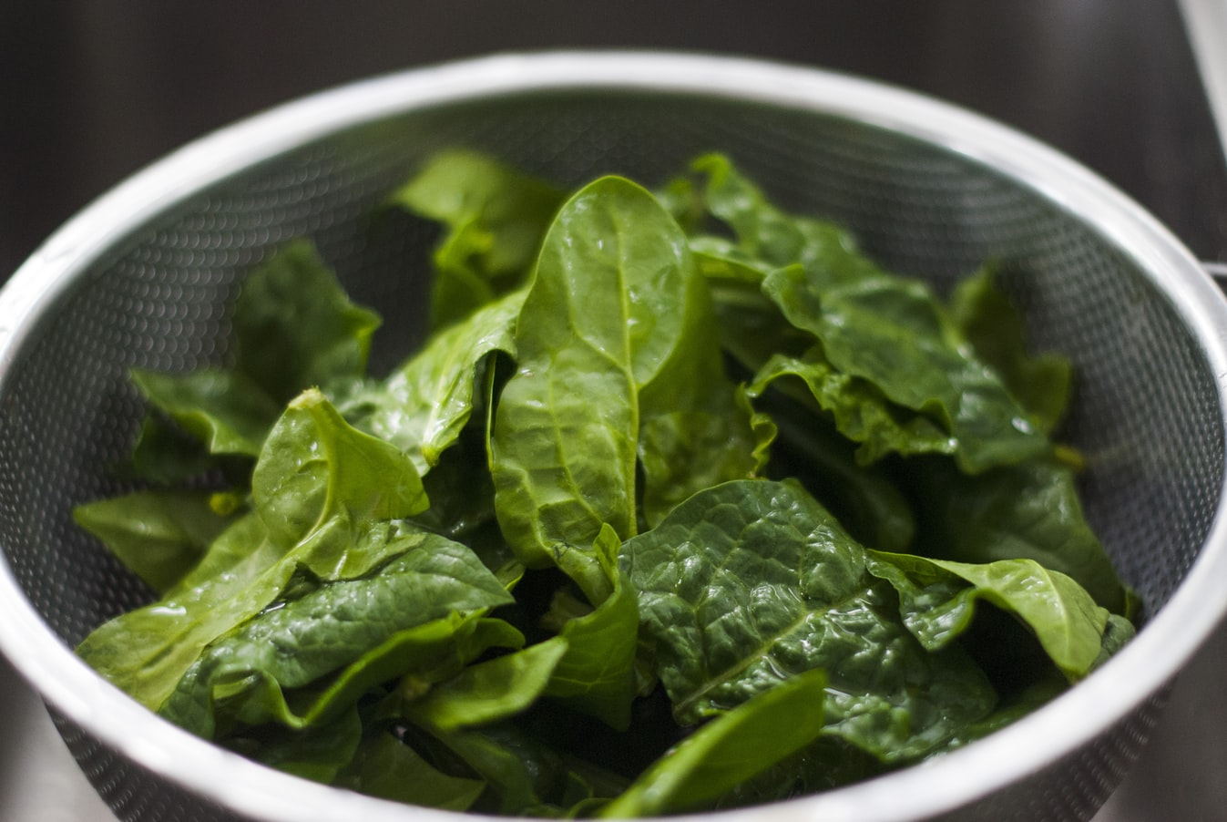A strainer filled with fresh spinach leaves