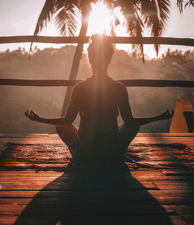 Woman practicing self care by meditating in the sunlight