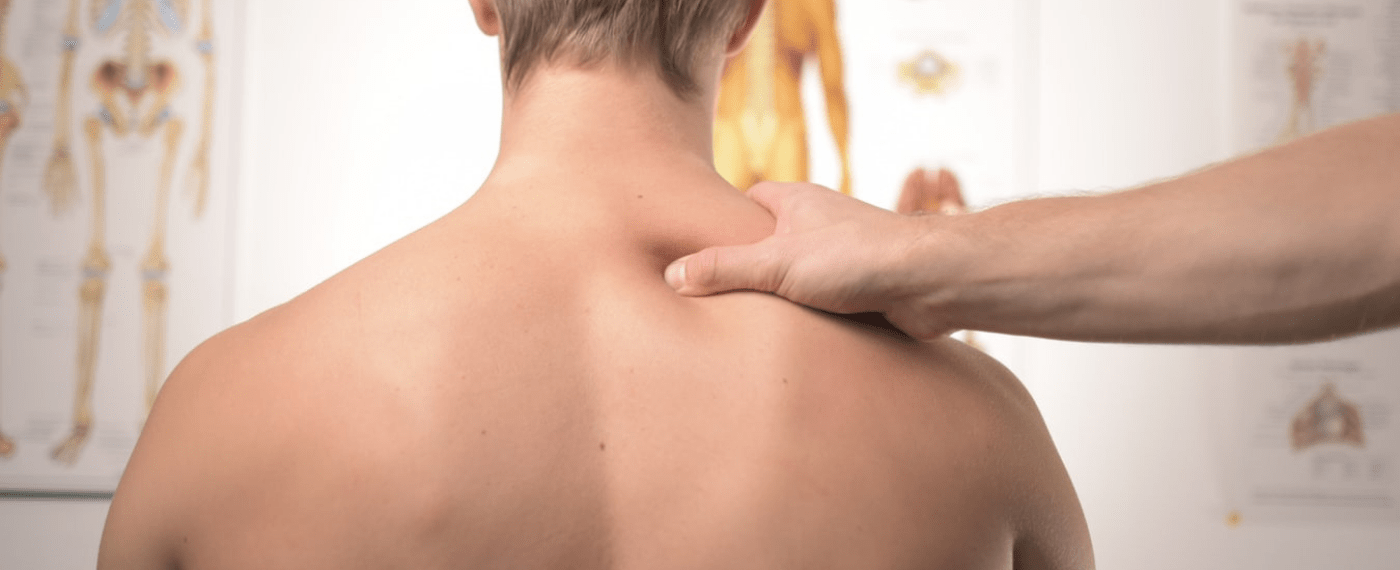 Shirtless male in doctors office getting his shoulder checked out by physician