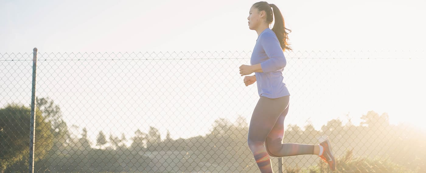 Woman in fitness gear running alongside chain-link fence with the sun in the background