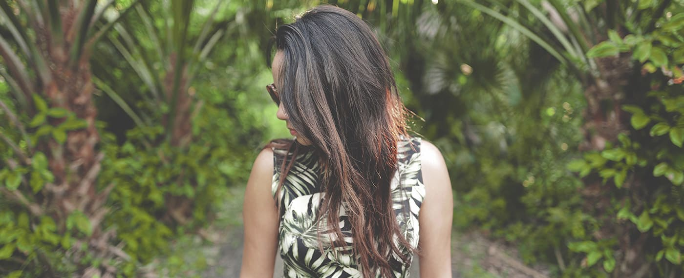 Woman wearing forest print dress with head turned in front of palm trees