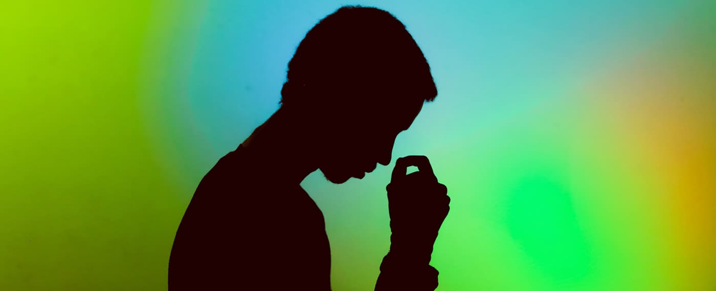 Shadowed image of a man with his head down to his hand