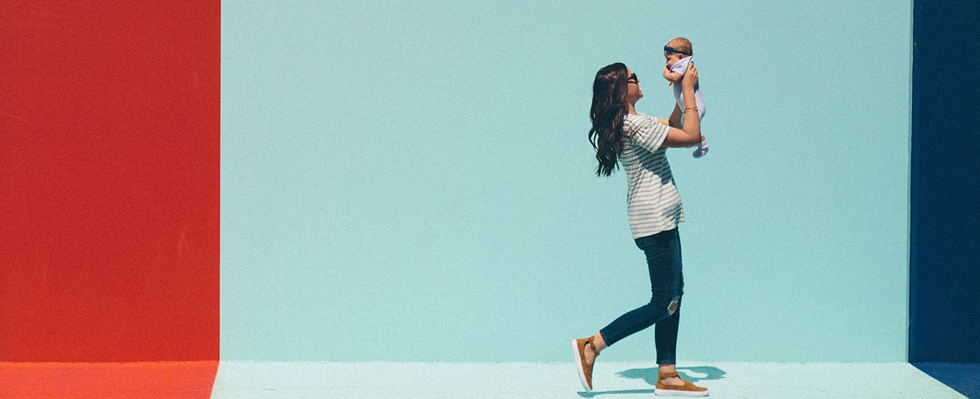 Woman walking while holding and looking up at newborn baby