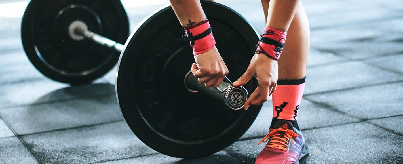 Woman with wrist straps putting clips on weight bar