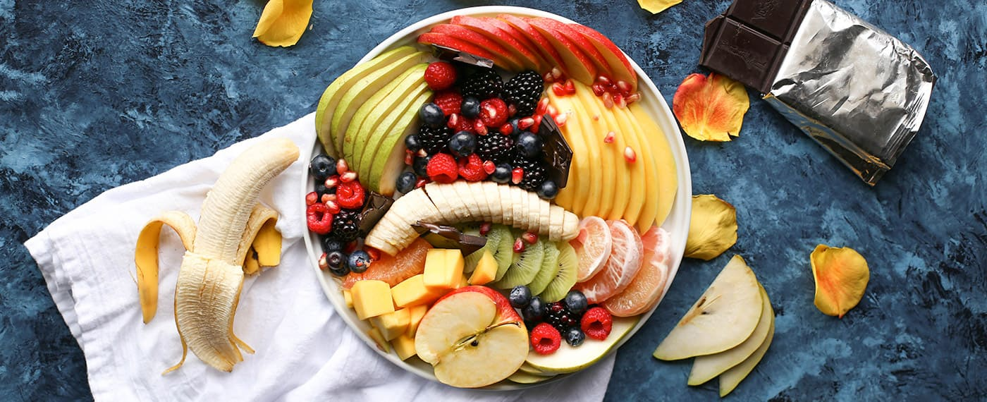 A bowl of antioxidant rich foods including bananas, berries, apples, and mango