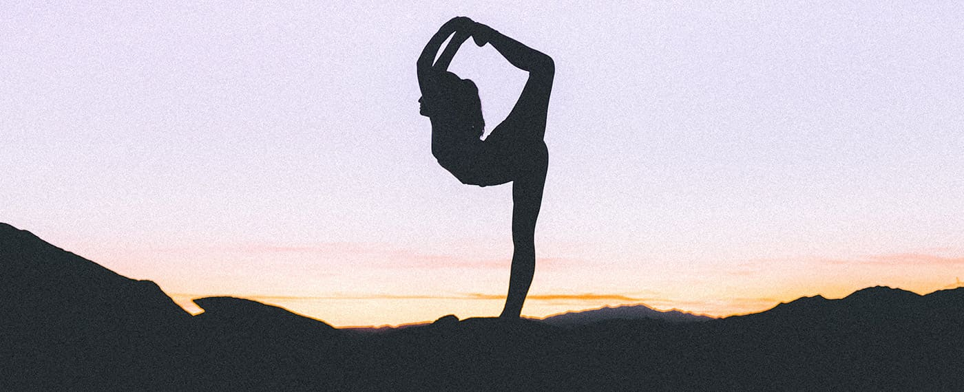 Woman performing natarajasana yoga pose with the sun setting