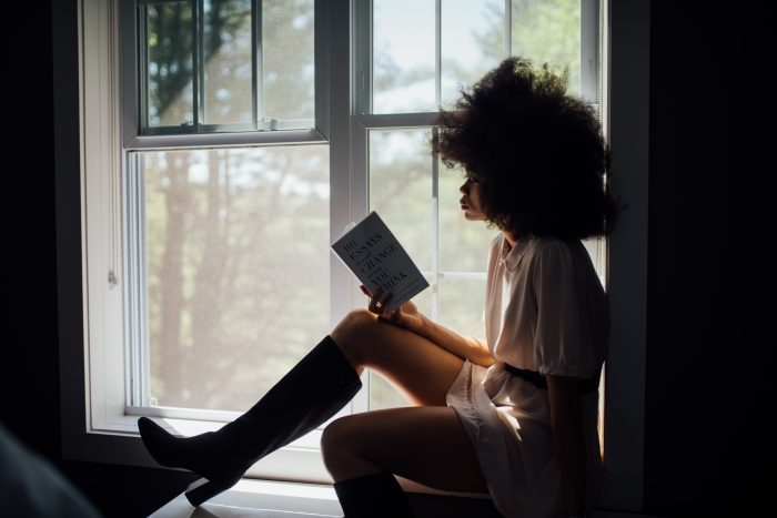 Girl sitting by an open window reading self care book
