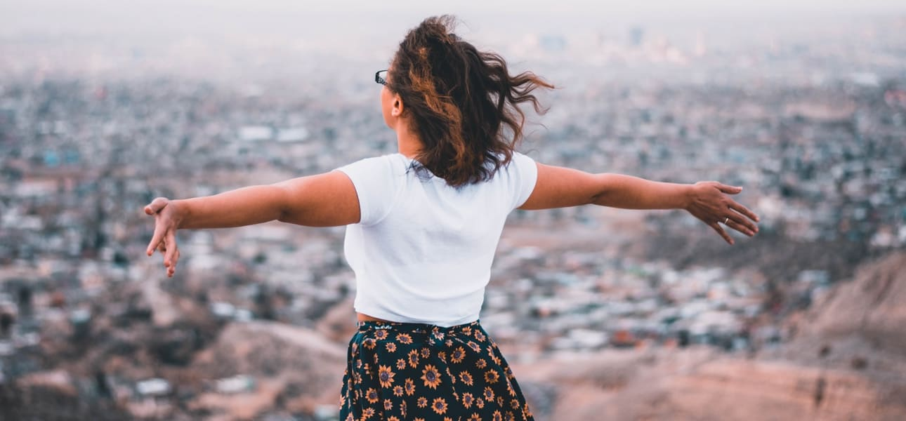 A woman at high altitude standing with arms outstretched
