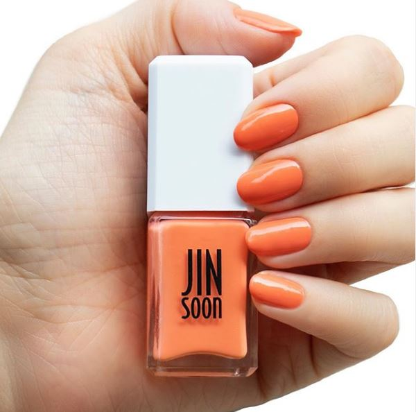 Female hand with bright orange nails holding a bottle of Jin Soon nail polish