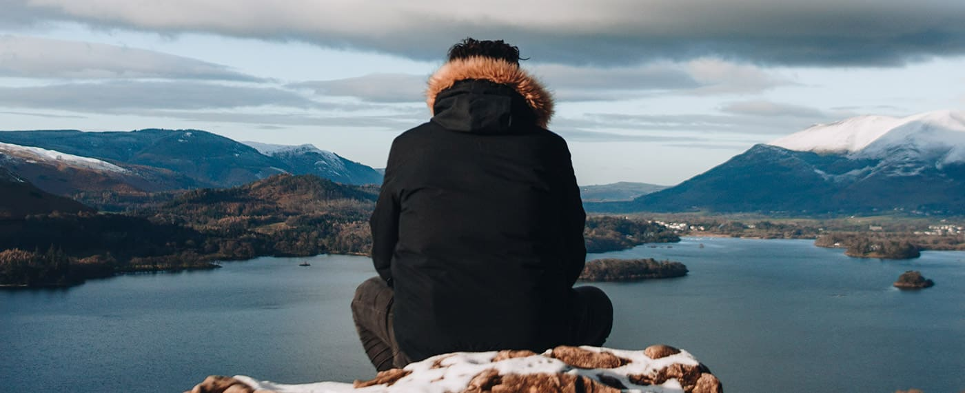Man sitting on snowy hilltop looking out at lake and snowy mountain tops