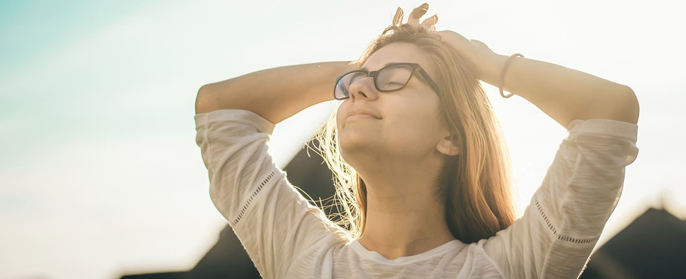 woman closing eyes and taking deep breathe with sunlight in the background to relieve stress