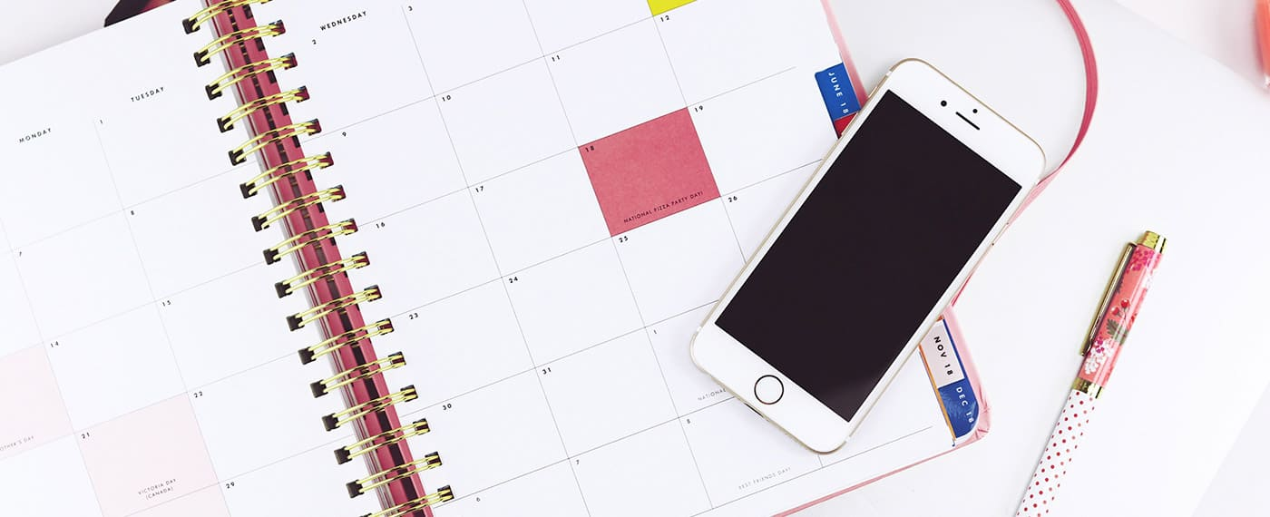 A daily planner with an iPhone lying on top