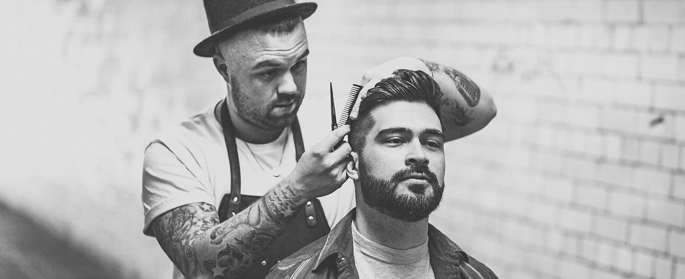 Barber with scissors and comb grooming a man's hair