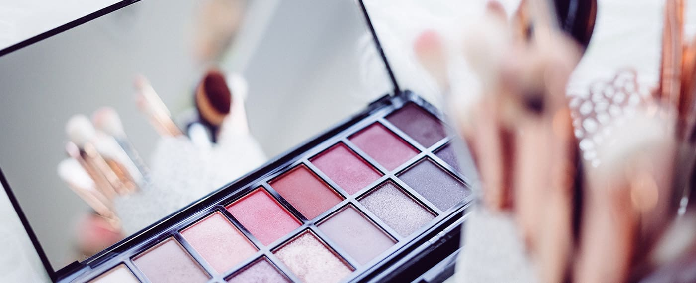 A makeup palette with makeup brushes reflecting in the mirror
