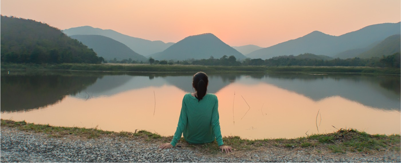 Woman sitting and being mindful of the peaceful lake water and scenery