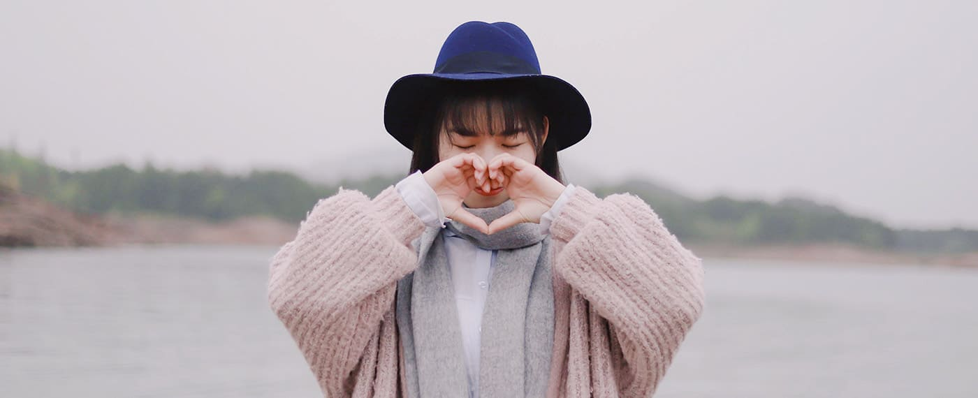 Girl with blue hat and pink sweater standing in front of lake making shape of heart with hands