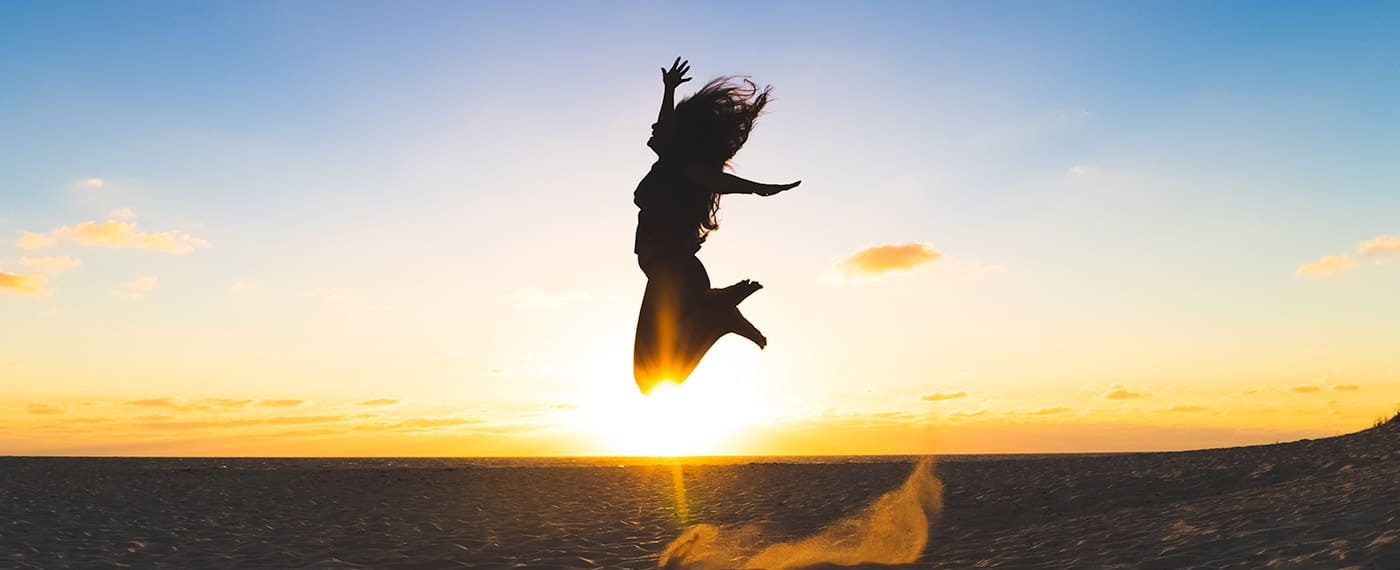 Woman jumping into the air with the sunset in the background