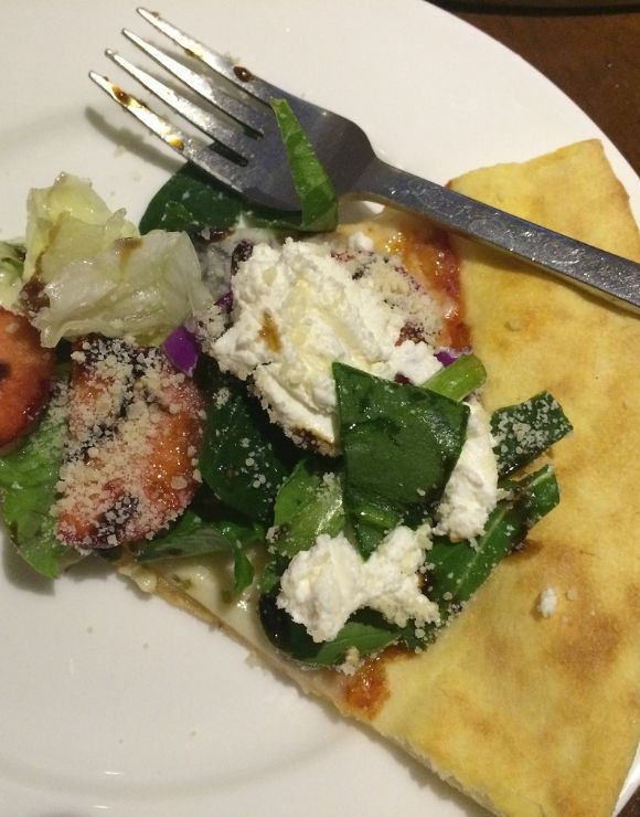 reheated flatbread pizza with salad, tomatoes, and cheese