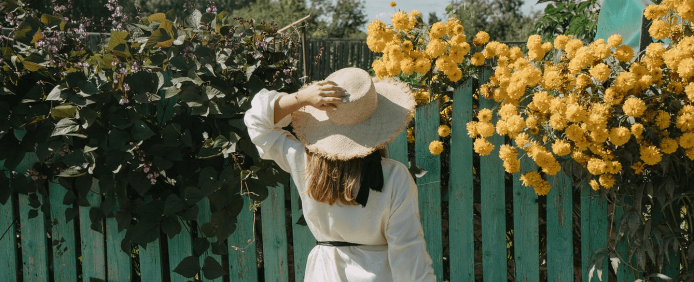 woman with straw hat looking at yellow flowers growing through a wooden fence