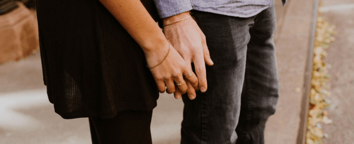 woman taking hold of man's hand