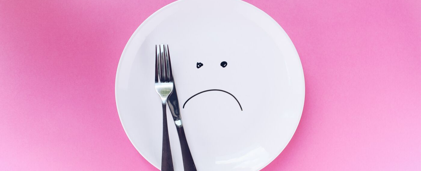 An empty plate with sad face drawn in the center