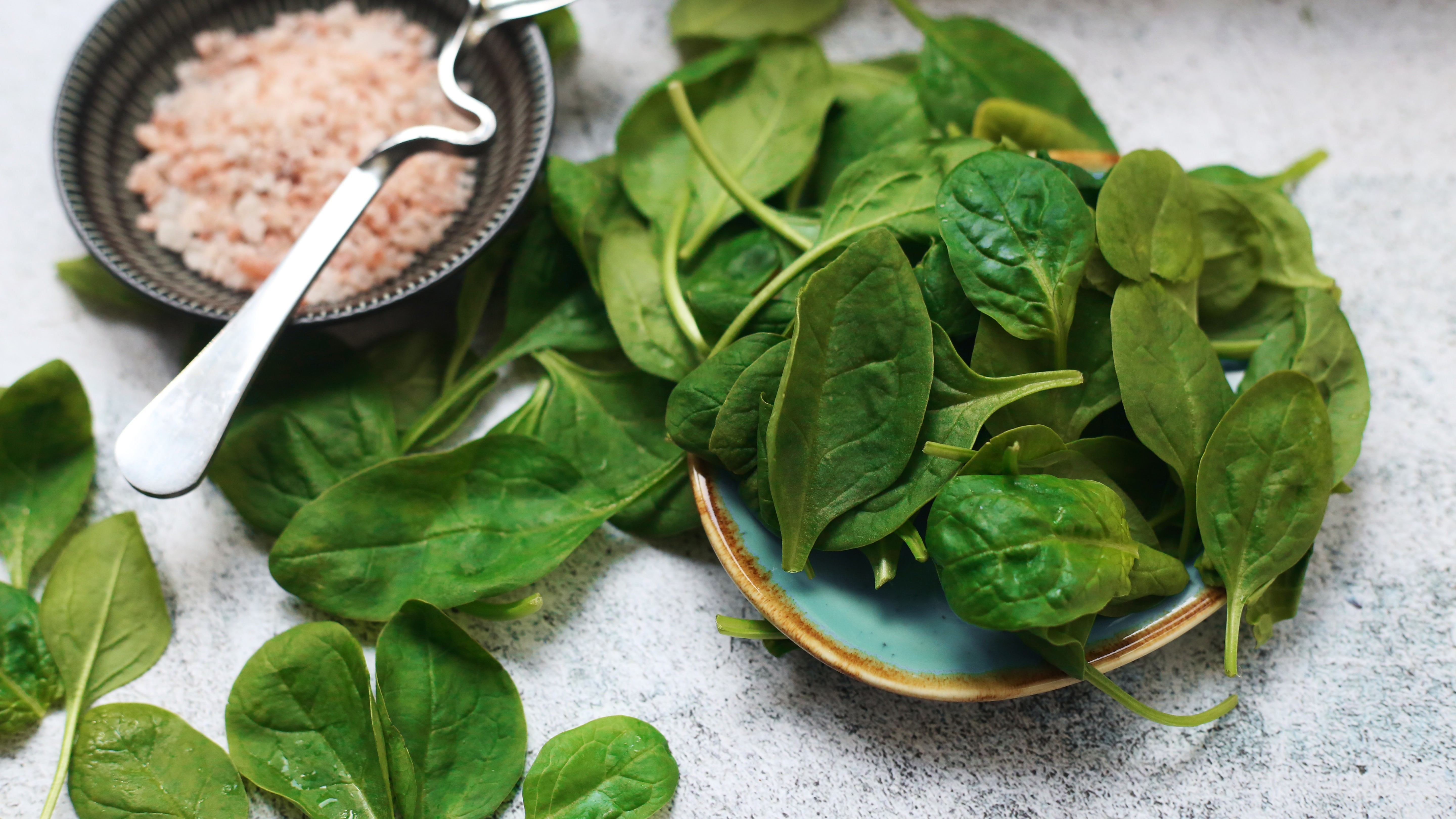 A bowl of leafy greens next to a bowl of grains