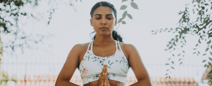 Woman meditating with hands folded against her chest