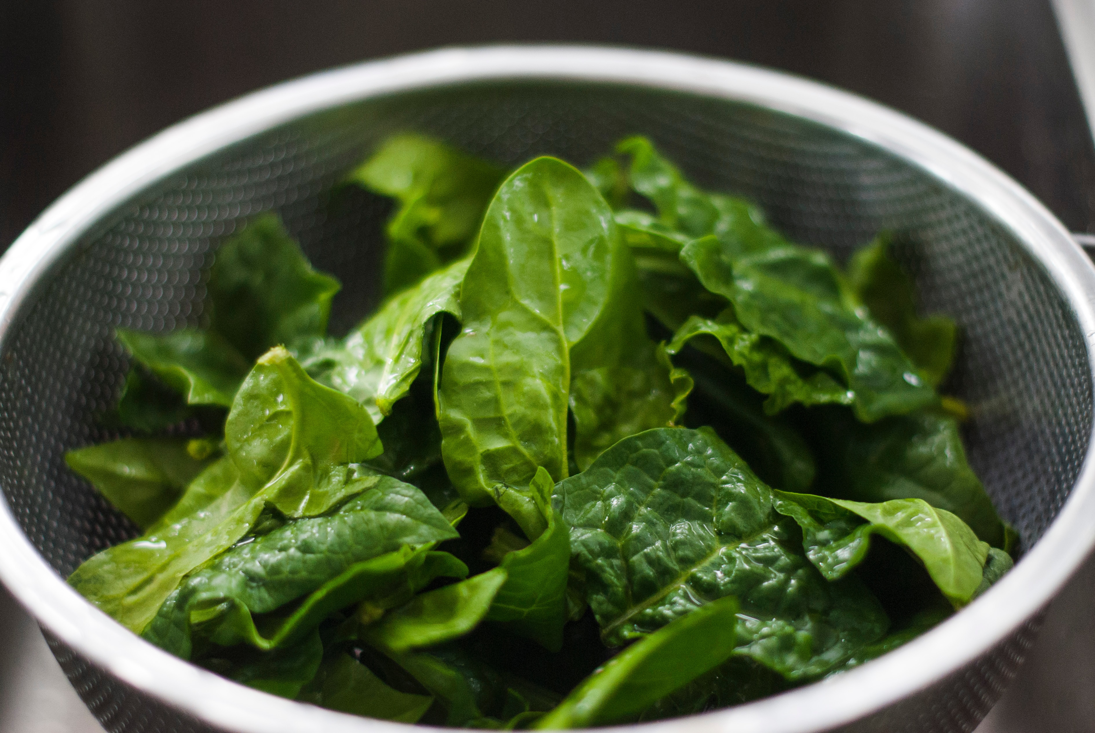 A metal strainer filled with spinach leaves