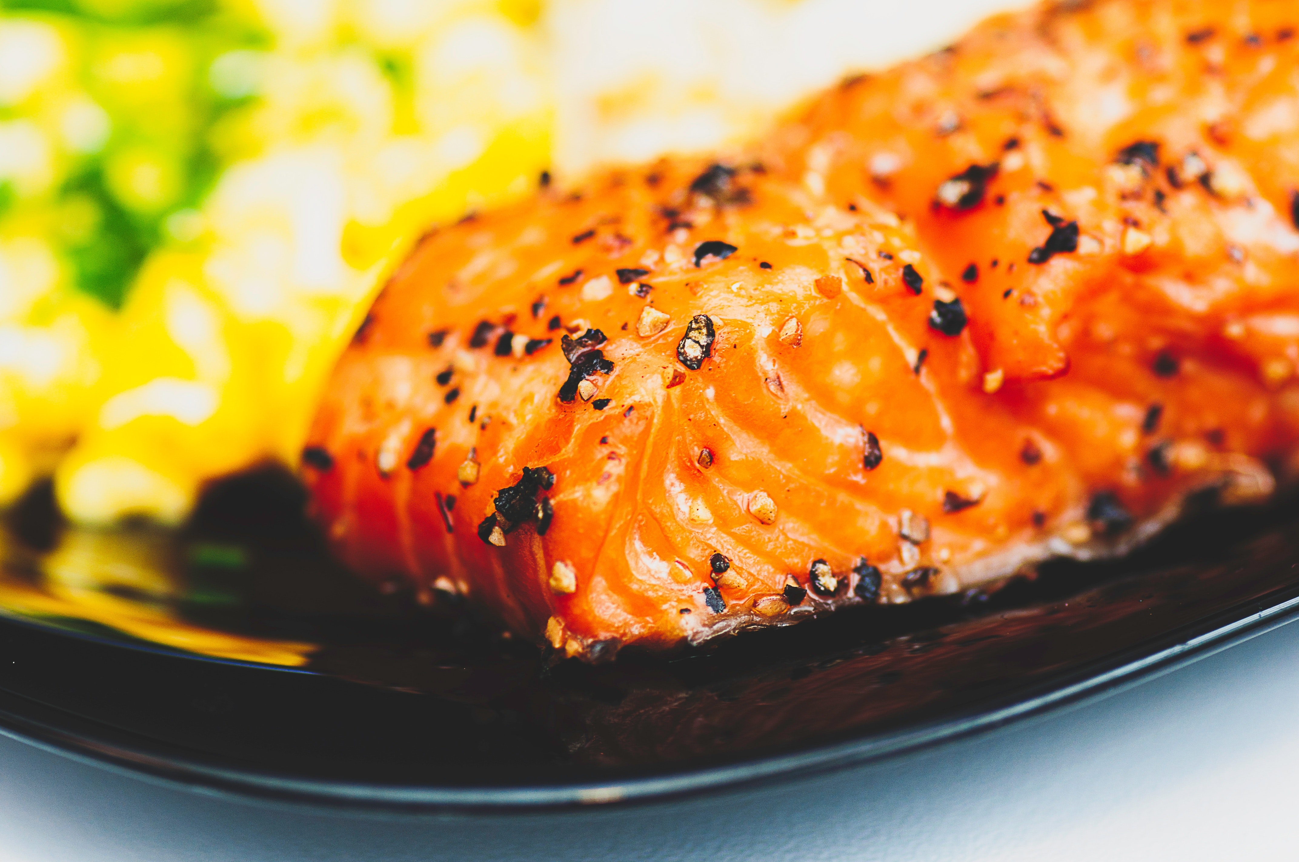 A plate of seared salmon with peppercorn flakes